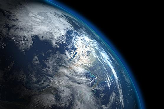 The Earth viewed from outer space, with a blue halo on its horizon.