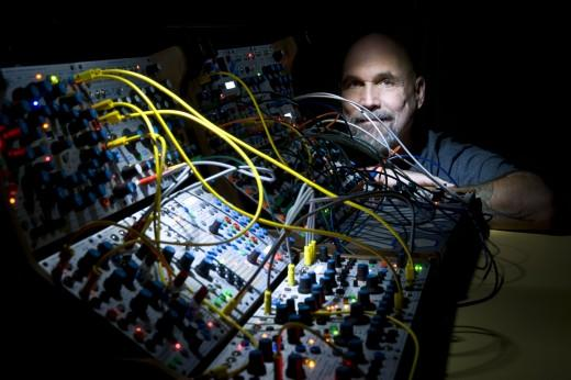 Bob Ostertag with a Buchla 200 synthesizer, with many yellow wires attached.