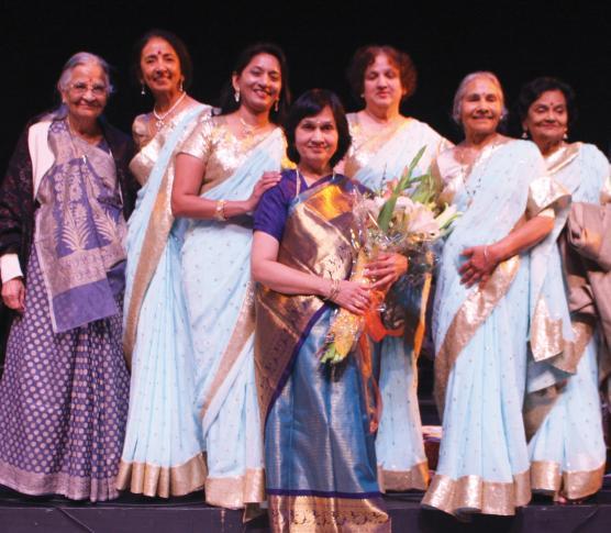 Rita Sahai, holding flowers, with the singers of the Vasundhara Choir.