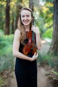 Devon Bradshaw, holding her violin in the arboretum.
