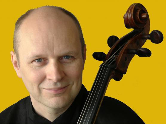 Anssi Karttunen with his cello on a yellow background.
